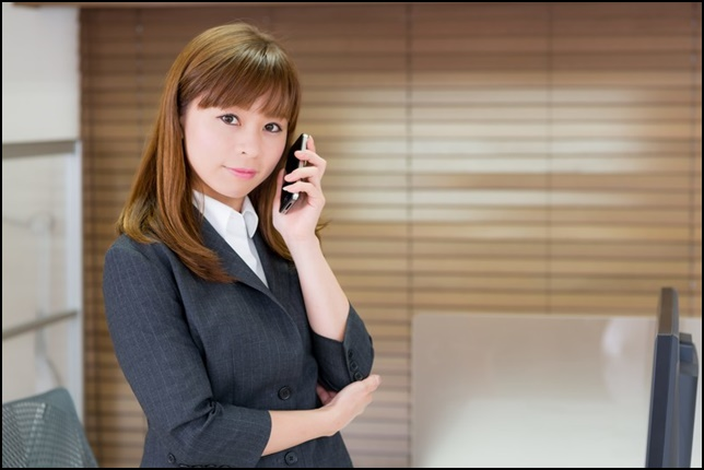 美人OLがスマホ・携帯電話で対応している画像