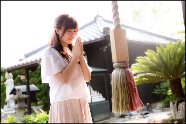 神社でお祈りしている女性の画像